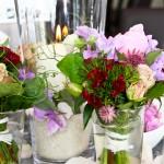 Tischdekoration mit Sträusse aus verschiedenen Blumen in rosatönen